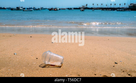 Rubbish Plastic cup left on the beach make pollution. - Stock Image