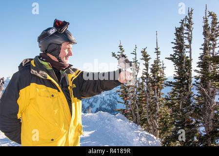 USA, Washington State, Crystal Mountain Resort. Gray Jays (Perisoreus canadensis) bold beggars. Perches on man's hand in hopes of food. (MR) - Stock Image
