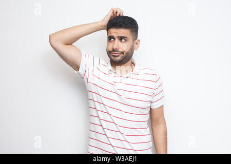 Portrait of query handsome bearded young man in striped t-shirt standing scratching his head, planing and thinking about something. indoor studio shot - Stock Image