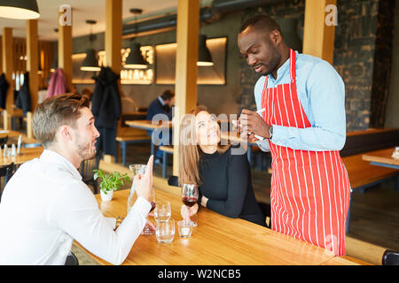 African waiter records order of guests couple on a notepad - Stock Image