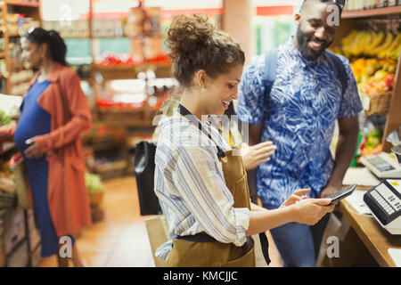 Female cashier with calculator helping male customer in grocery store - Stock Image