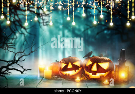 Spooky halloween pumpkins on wooden planks with dark horror background. Celebration theme, copyspace for text. - Stock Image