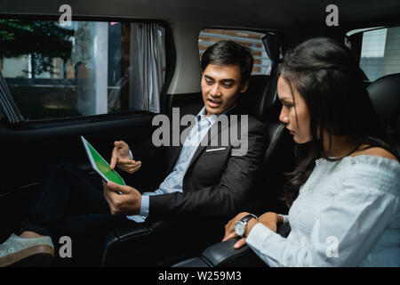 young business people meeting in the car. busy team discuss on passenger seat of a car - Stock Image