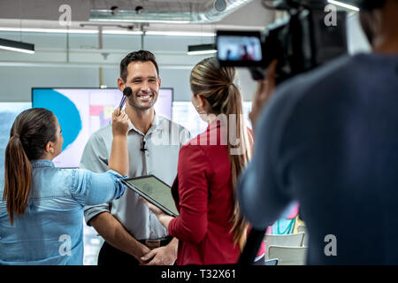 Camera Recording Video Of Businessman Corporate Interview And Makeup Artist - Stock Image