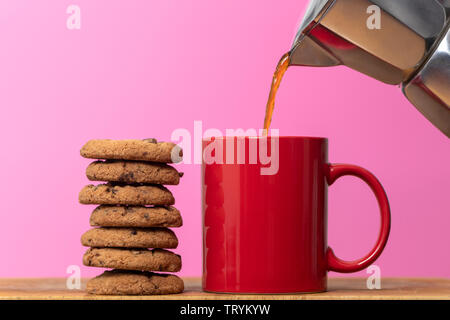 coffee being poured int a red mug with a stack of chocolate chip cookies - Stock Image