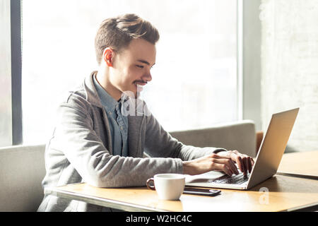 Portrait of handsome cheerful bearded young businessman in grey blazer are sitting in cafe and typing message with toothy smile and looking at laptop. - Stock Image