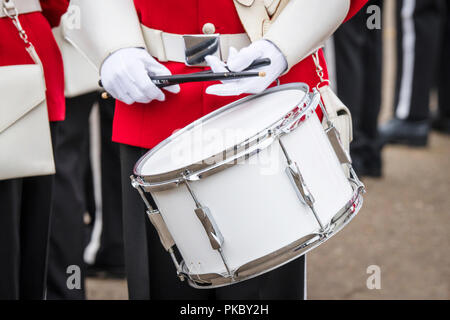 Soldier drummer in red uniform and white gloves playing drum in a march - Stock Image