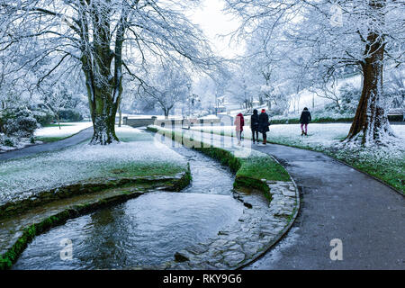 People enjoying a walk in the snow in Trenance Gardens in Newquay in Cornwall. - Stock Image