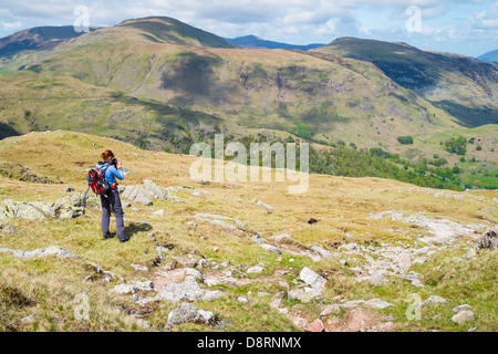A female hiker taking a photograph while descending from the summit of Glaramara towards Thornythwaite Fell in the - Stock Image