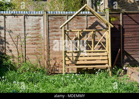 English back garden on a sunny day with wooden arbour bench. - Stock Image