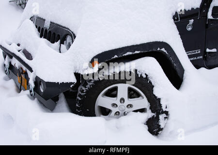 A black Jeep Wrangler Sport covered with snow after a blizzard in Speculator, NY USA - Stock Image