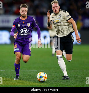 Optus Stadium, Perth, Western Australia. 13th July, 2019Optus Stadium, Perth, Western Australia. 13th July, 2019. Pre-season friendly football, Perth Glory versus Manchester United; Chris Harold of the Perth Glory runs with the ball as Phil Jones of Manchester United moves in to tackle Credit: Action Plus Sports/Alamy Live News Credit: Action Plus Sports Images/Alamy Live News - Stock Image
