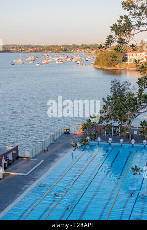 Set directly below the Iron Cove Bridge on the banks of the Parramatta River, early morning swimmers complete laps at the Drummoyne Swimming Centre. - Stock Image