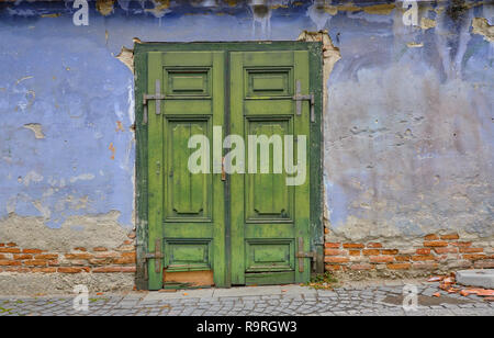 Century old crumbling blue plastered wall over brick, with a green door, - Stock Image