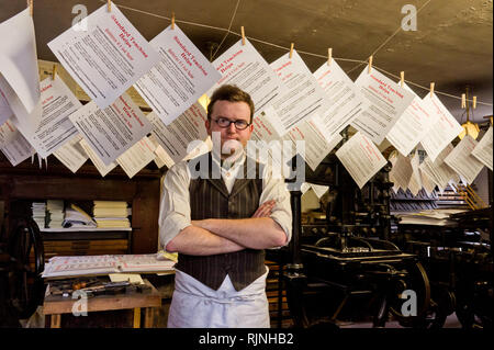 Print worker in period costume in front of some drying prints, Blists Hill Victorian Town, Shropshire, UK - Stock Image