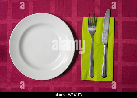 White plate, fork and knife on a napkin. Red tablecloth. View from above - Stock Image