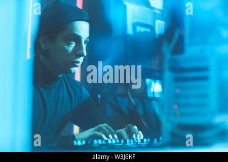 Serious concentrated young Jewish hacker in beanie hat sitting at table in dark room and typing on keyboard while breaking into server data - Stock Image