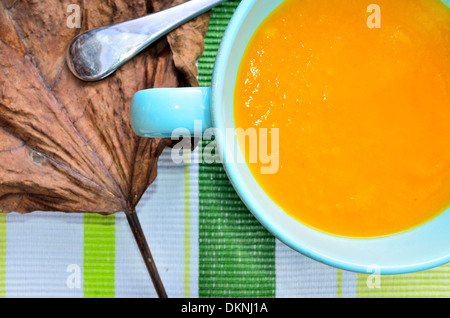 pumpkin soup with green placemat and brown leaf - Stock Image