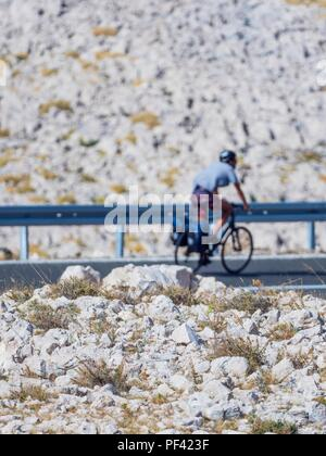 Rocky rough terrain on Pag island and out-of-focus bicyclist in background - Stock Image