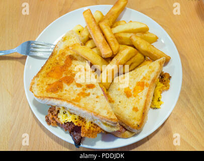 Supermarket café lunch snack toasted bacon and cheese sandwich  with grilled cheese on top served with potato chips - Stock Image
