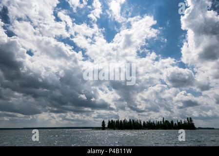 Sun sparkles on island surrounded by lake, Dore Lake, Saskatchewan, Canada - Stock Image