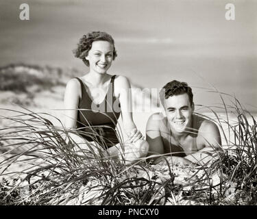 1930S SMILING MAN WOMAN COUPLE LYING IN BEACH SAND LOOKING AT CAMERA OVER DUNES GRASS - b13740 HAR001 HARS FEMALES MARRIED SPOUSE HUSBANDS HEALTHINESS FRIENDSHIP HALF-LENGTH LADIES PERSONS MALES CONFIDENCE B&W EYE CONTACT BRUNETTE TIME OFF SHORE HAPPINESS CHEERFUL LEISURE GETAWAY DUNES HANDSOME BEACHES HOLIDAYS SMILES DUNE JOYFUL SANDY TOGETHERNESS VACATIONS WIVES YOUNG ADULT MAN YOUNG ADULT WOMAN BLACK AND WHITE CAUCASIAN ETHNICITY HAR001 OLD FASHIONED - Stock Image