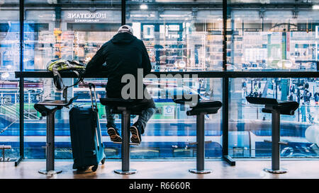 Paris, France - Nov 15, 2018: One man sits next to his luggage at a cafe overlooking passengers and trains below at Paris's Gare du Nord station - Stock Image
