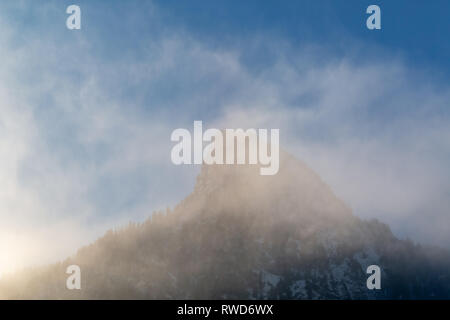 Mist forms around the Kofel, the distinctive mountain in Oberammergau, Bavaria. - Stock Image