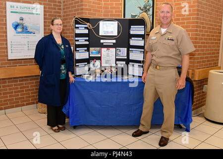 180830-N-IY469-002 – Holly LaPerriere and Capt. Chris Kuzniewski set up a booth to promote their research on lung cancer. LaPerriere is a research nurse and coordinator and Kuzniewski is the primary investigator for Detection of Early Lung Cancer Among Military Personnel (DECAMP). - Stock Image