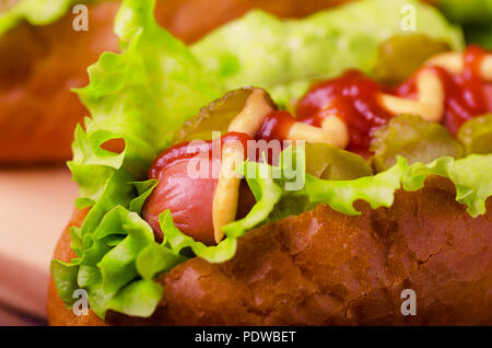 Hot dog with mustard and ketchup, close-up on a wooden background - Stock Image