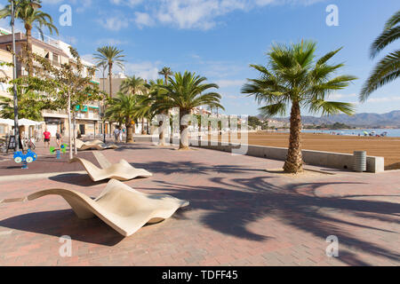 Puerto de Mazarron Spain visitors enjoying the beautiful Spanish beach, palm trees and winter sunshine - Stock Image