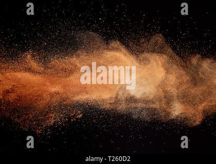 Cocoa powder explosion on black background. - Stock Image