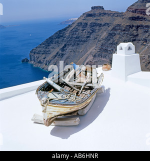 A fishing boat on a rooftop above volcanic cliffs in Santorini Greek Islands, Greece  KATHY DEWITT - Stock Image