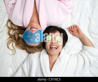 Women in bathrobes wearing eye masks - Stock Image