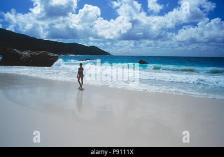 BEACH WITH FIGURE WALKING ON THE SAND AND ISLAND VIEW, SEYCHELLES, ISLAND, EAST AFRICA. JUNE 2009. The beautiful islands of the Seychelles in the Indi - Stock Image