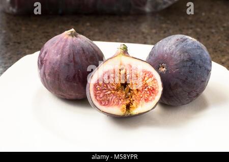 Three fresh Black Bursa ripe figs, one halved to show inside flesh and seeds - Stock Image