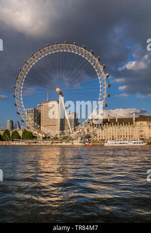 The London Eye, Marriott County Hall and Shell HQ from Westminster Pier Victoria embankment reflected in River Thames Westminster London England UK - Stock Image