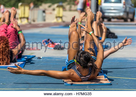 Women enjoying a fitness doing crunches class outdoor on a sunny day. - Stock Image