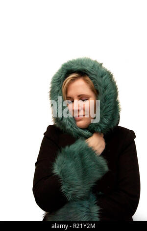 Beautiful model with gorgeous green and black winter coat wrapped around her face in comfort - Stock Image
