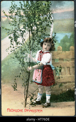 GERMANY - CIRCA 1916: A postcard printed in Germany, shows a beautiful little girl on the background of the rural - Stock Image