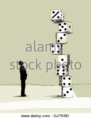 Businessman looking up at percentage sign on top of tall pile of large dice - Stock Image