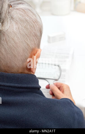 Old woman sitting at a table in her living room using a magnifying glass to read the information sheet of her prescribed medicine - Stock Image