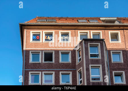 Exterior of old apartment building with 'No Racism' lettering on top storey windows in Mitte, Berlin - Stock Image