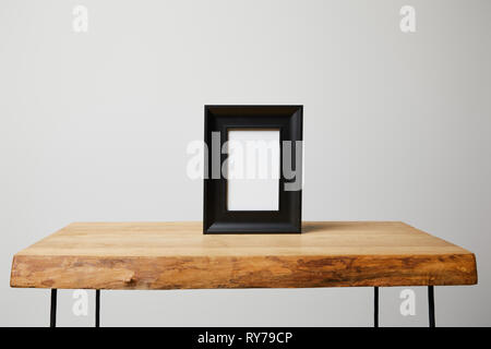 black square frame on wooden table at home - Stock Image