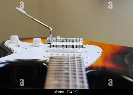 Looking down the neck and over the bridge, scratch plate and vibrato arm of an electric guitar. - Stock Image