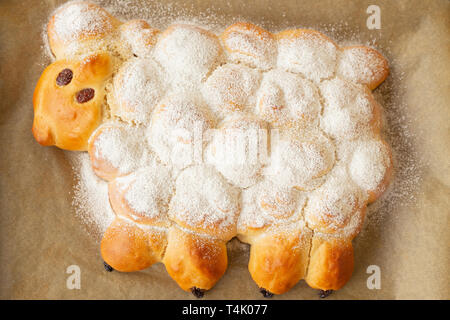 Vegan easter lamb based on yeast dough decorated with powdered sugar and raisins - Stock Image