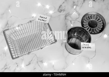 ecology and consumerism concept: spend better for less waste shopping basket next to gargabe bin and fairy lights on marble desk - Stock Image