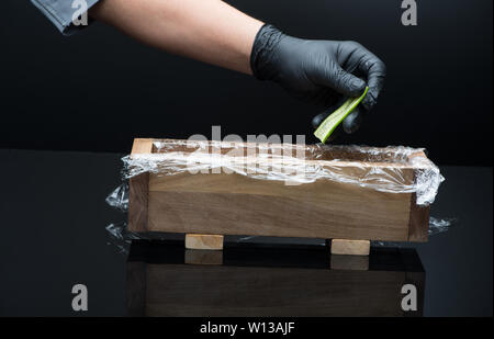 chef prepares sushi, puts cucumber in a wooden mold - Stock Image