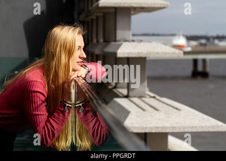 Dundee, Tayside, Scotland, UK. 25th September, 2018. UK weather: Strong winds with light rain sweeping across Tayside. A young woman Rhianna Martin pays her first visit to the stunning new V&A building gracing the skyline from the Museum balcony on a very blustery day in Dundee,UK. Credits: Dundee Photographics / Alamy Live News - Stock Image