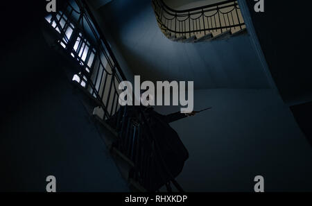 Young man stands on stairs in image of black magician with magic wand in his hand. - Stock Image